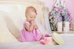 La niña en un vestido rosado con la flor en su pelo sonríe y abre los regalos de la caja en cama el fondo de la Navidad Fotografía de archivo libre de regalías