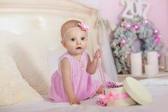 La niña en un vestido rosado con la flor en su pelo sonríe y abre los regalos de la caja en cama el fondo de la Navidad Fotografía de archivo