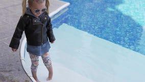 La niña en una chaqueta de cuero moja pies en la piscina almacen de video