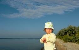 La niña en una orilla de la soledad Fotos de archivo