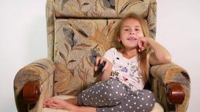 La niña en una silla del sofá cambia los canales con teledirigido e imita lo que ella vio almacen de metraje de vídeo
