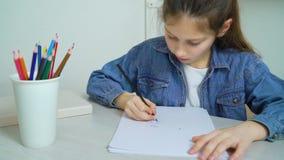 La niña en vaqueros lleva el dibujo con el lápiz coloreado en casa almacen de video