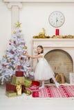 La niña en vestido hermoso adorna el árbol de navidad Imagen de archivo libre de regalías