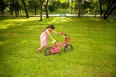 La niña en vestido rosado empuja su bici en la hierba en el parque foto de archivo libre de regalías