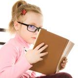 La niña en vidrios con un libro Imagenes de archivo
