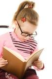 La niña en vidrios con un libro Fotos de archivo