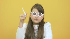 La niña en vidrios plásticos muestra las tijeras de un plástico en fondo amarillo metrajes