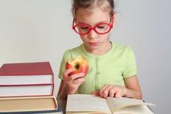 La niña en vidrios rojos leyó el libro Imagen de archivo libre de regalías