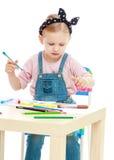 La niña encantadora dibuja con los marcadores mientras que Imagenes de archivo