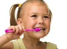 La niña es dientes de la limpieza usando el cepillo de dientes Imagenes de archivo