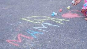 La niña escribe a la mamá de la palabra por la tiza en el asfalto Concepto de familia fotos de archivo