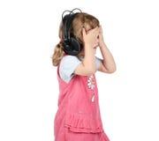 La niña escucha la música en auriculares grandes y ojos cerrados Imagen de archivo