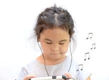 La niña escucha música con soplar de la nota de la canción Fotografía de archivo