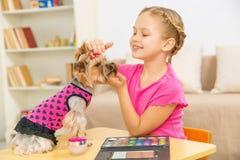 La niña está acariciando su animal doméstico Imagen de archivo libre de regalías