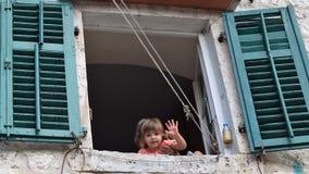 La niña está agitando la mano de la ventana fotos de archivo libres de regalías