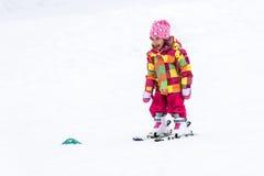 La niña está aprendiendo esquiar en estación de esquí Foto de archivo