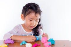 La niña está aprendiendo utilizar la pasta colorida del juego Fotografía de archivo libre de regalías