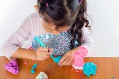 La niña está aprendiendo utilizar la pasta colorida del juego Imagenes de archivo
