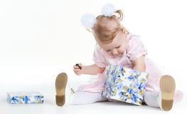 La niña está buscando un presente en una caja Foto de archivo