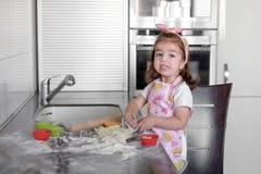 La niña está cocinando en cocina Divertirse mientras que hace las tortas y las galletas imagenes de archivo