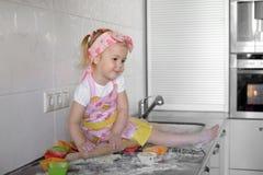 La niña está cocinando en cocina Divertirse mientras que hace las tortas y las galletas foto de archivo