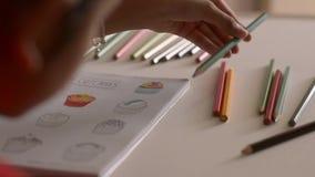 La niña está coloreando imágenes en un libro con el lápiz coloreado almacen de video