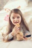 La niña está comiendo las galletas de harina de avena en cama Imagen de archivo