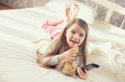 La niña está comiendo las galletas de harina de avena en cama Fotos de archivo