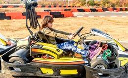 La niña está conduciendo el coche del kart en una pista que compite con del patio Foto de archivo