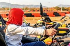 La niña está conduciendo el coche del kart en una pista que compite con del patio Fotos de archivo libres de regalías