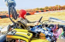 La niña está conduciendo el coche del kart en una pista que compite con del patio Fotografía de archivo