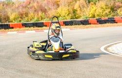 La niña está conduciendo el coche del kart en una pista que compite con del patio Fotos de archivo