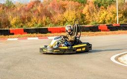 La niña está conduciendo el coche del kart en una pista que compite con del patio Imagenes de archivo