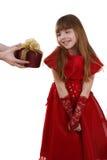 La niña está consiguiendo el regalo. La muchacha siente tímida. imagenes de archivo