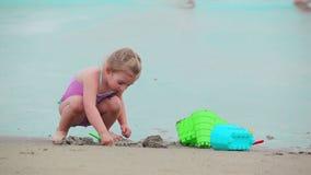 La niña está construyendo castillos de una arena en la playa almacen de metraje de vídeo