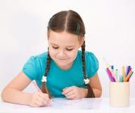 La niña está dibujando con los lápices foto de archivo