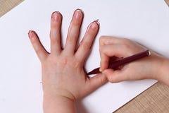 La niña está dibujando el contorno de la mano. Imagenes de archivo