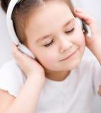 La niña está disfrutando de música usando los auriculares Foto de archivo libre de regalías