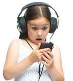 La niña está disfrutando de música usando los auriculares Imagenes de archivo