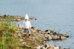 La niña está en el riverbank imagenes de archivo
