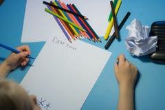La niña está escribiendo una letra a Papá Noel imagen de archivo libre de regalías
