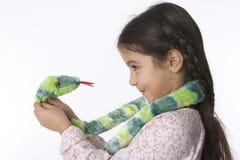La niña está hablando con una serpiente del juguete Imagen de archivo libre de regalías