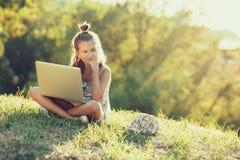 La niña está hablando en un ordenador portátil mientras que se sienta en la hierba en el sol Vestido en un sarafan y un sombrero imágenes de archivo libres de regalías