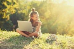 La niña está hablando en un ordenador portátil mientras que se sienta en la hierba en el sol Vestido en un sarafan y un sombrero foto de archivo
