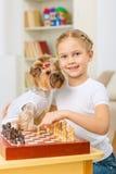 La niña está jugando a ajedrez con su perro Imagenes de archivo