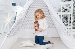 La niña está jugando con el pequeño perro de perrito cerca de la tienda india en sala de juegos de la Navidad foto de archivo