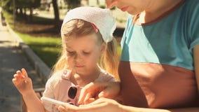 La niña está jugando en un smartphone que miente en las manos de su mamá al aire libre