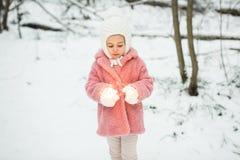 La niña está llevando a cabo las luces de Bengala en el invierno en bosque Imagen de archivo libre de regalías