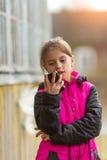 La niña está mecanografiando en el smartphone que se coloca al aire libre Feliz Fotografía de archivo libre de regalías