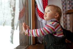 La niña está mirando hacia fuera la ventana Imagenes de archivo